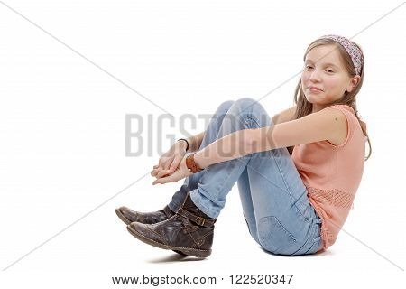 a young preteen sitting on the floor on white