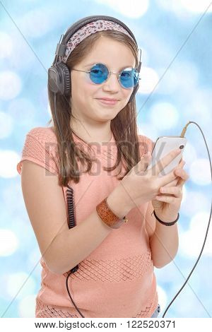 A preteen girl listening to music with his smartphone bokeh background