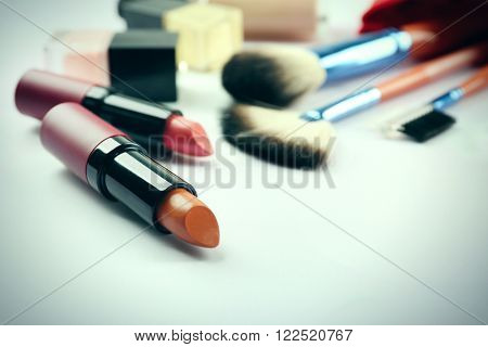 Makeup set with brushes and lipsticks on light background