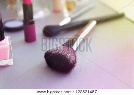 Makeup brush with cosmetics on a table, close up
