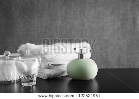 Bathroom set with towels, dispenser and sponges on grey background