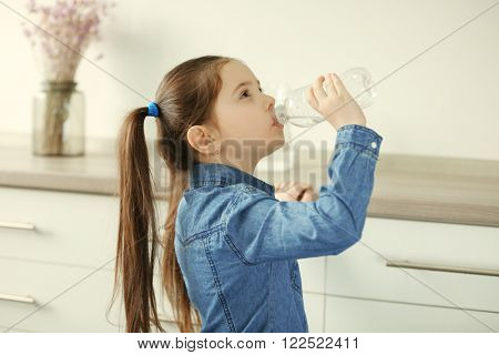 Little girl drinking water from plastic bottle in living room