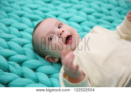 Lovely baby on knitted turquoise background, close up