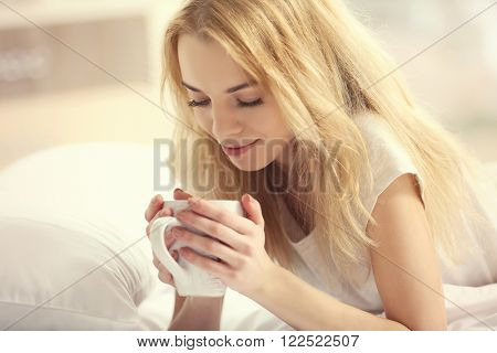 Attractive young blonde girl in a pajama enjoying her morning drink while laying in bed