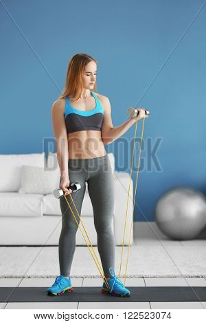 Young sportswoman doing exercises with rubber band and dumbbells on a mat at home