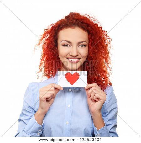Red-haired young woman holding paper red heart, isolated on white