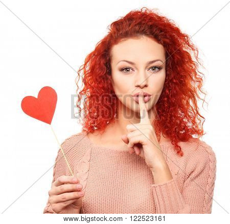 Red-haired young woman holding paper heart, isolated on white