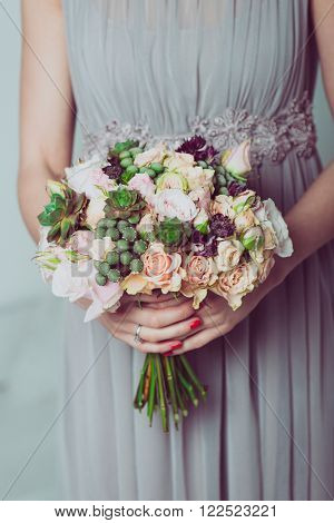 Close up image of bridesmaid with a bouquet of wedding flowers