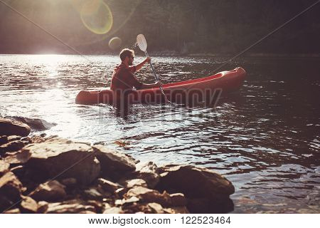 Young man kayaking in a lake. Young guy paddles his kayak on a sunny day.