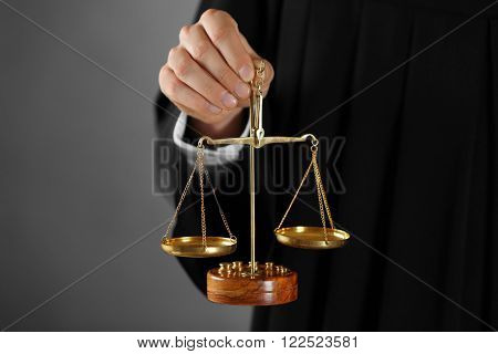 Judge holding scales of justice on grey background