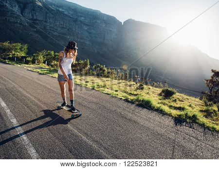 Young woman skating outdoors on rural road. Female longboarding on a summer day.
