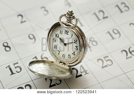 Vintage silver pocket watch laying on calender page with dates, close up