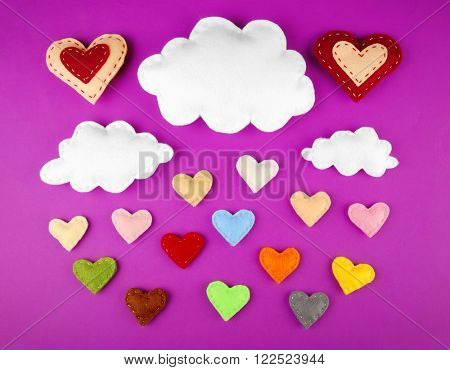 Varicolored fabric hearts and clouds on purple background