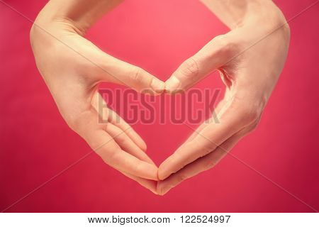 Male and female hands making heart with fingers on red background
