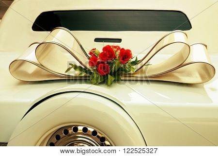 Limousine backside ornate with flowers. White wedding retro car closeup. Yellow toned.