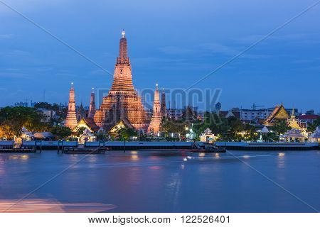 Large illuminated temple Wat Arun after sunset seen accross river Chao Phraya. Bangkok, Thailand