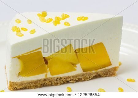Close Up Of Mango Cream Pie With Peeled Split Mung Bean On White Plate