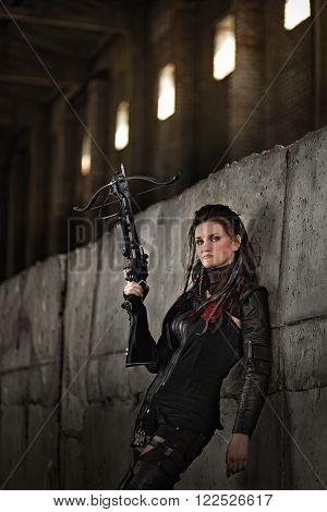 Tribal girl in leather costume with a crossbow in post-apocalyptic world.