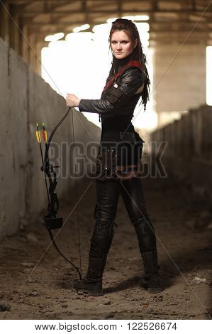 Young tribal girl in black leather costume with bow and arrow inside post-apocalyptic world.