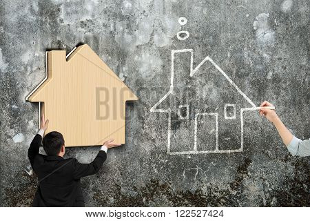 Man putting wooden house into hole of old mottled concrete wall, beside with woman hand drawing house doodles.