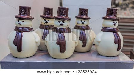 Brussels Belgium - January 17 2015: White and milk chocolate snowmen on display in the Leonidas store window at Christmas. Leonidas is a Belgian chocolate company with 350 shops in Belgium and 1250 stores in around the world