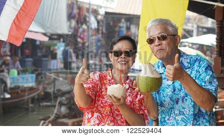 Asian senior couple travel to thailand floating market. Drinking frsh coconut juice