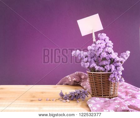 The sweet statice flower in basket with blank paper label on purple background and wooden table romance concept