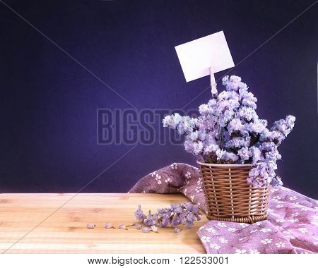 The sweet statice flower in basket with blank paper label on dark blue background and wooden table romance concept
