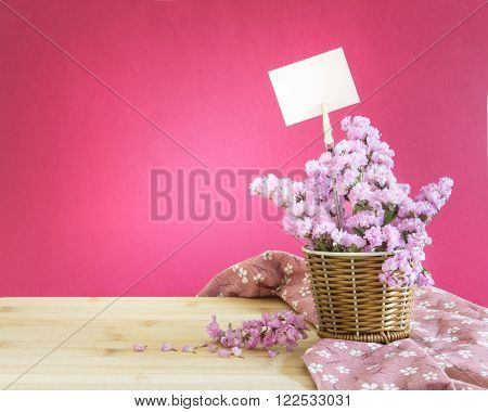 The sweet statice flower in basket with blank paper label on pink background and wooden table romance concept
