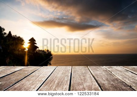 Wooden pier with de focus sunset at Tanah Lot cliff, in Bali