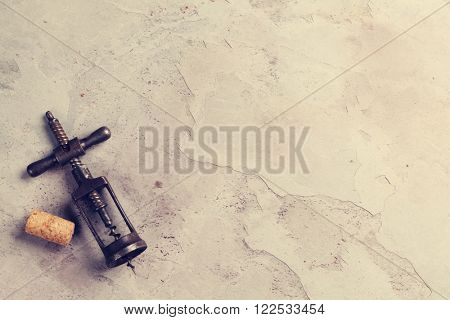 Vintage corkscrew and cork on stone table. Top view with copy space