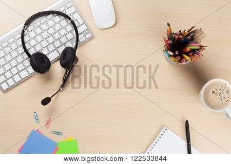 Office desk with headset, notepad and pc. Call center support table. Top veiw with copy space