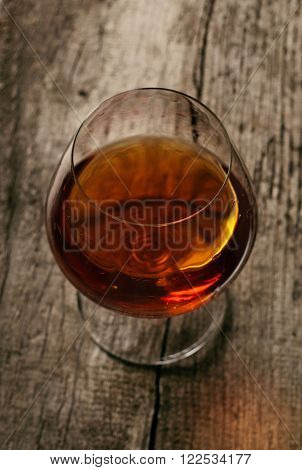 Closeup brandy in large round glass on the old wooden background. Top view