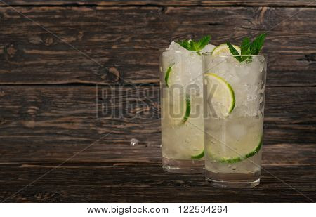two cocktails with white rum or gin with ice lime and mint in a tumbler glass on a dark wooden background with copy space. Summer cocktails background