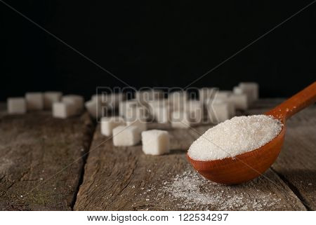 white sugar in a wooden spoon and sugar cubes closeup on a wooden table on a black background with copy space