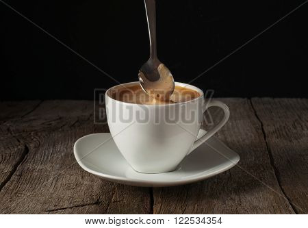 Closeup up of coffee with thick of crema on wooden table on black background with copy space. Coffee background