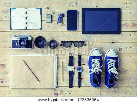 Outfit of a stylish traveler. Set of different objects and equipment: tablet, phone, album, glasses, camera, lenses, gumshoes and watches.