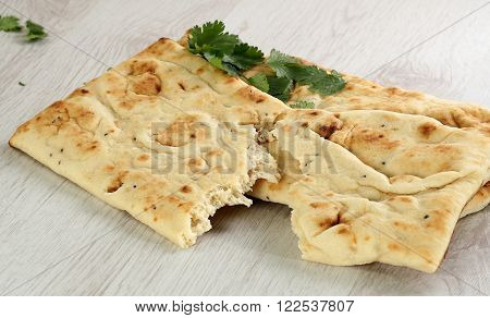 homemade oblong shaped naan bread with coriander