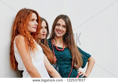 Girlfriends, sisters triplets Happiness portrait about light wall. focus is on second girl