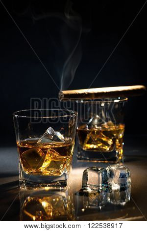 Glasses of whiskey with smoking cigar and ice cubes on dark background