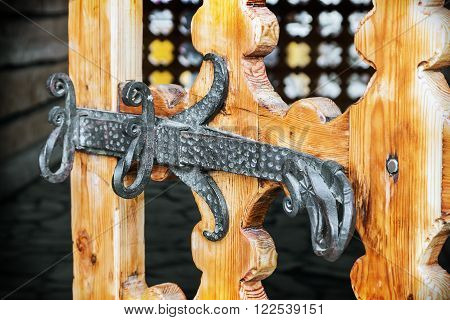 old carved wooden door. Focus on the middle of metal latch