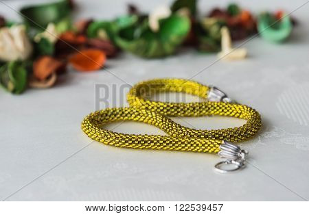 Shining Yellow Beaded Crochet Necklace On Textile Background