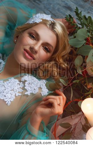 Charming young blond woman on the floor with candles and fresh flowers bouquet with roses carnations and eucalyptus leaves. Bridal boudoir.