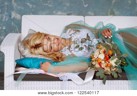 Bridal morning boudoir with smiling charming blond woman wearing mint transparent peignoir and holding fresh flowers ** Note: Visible grain at 100%, best at smaller sizes