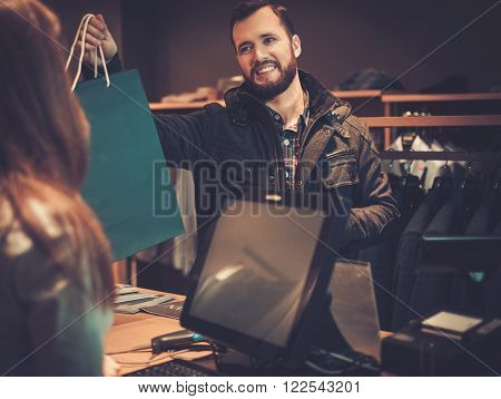 Happy handsome man taking shopping bag from saleswoman in a suit shop.