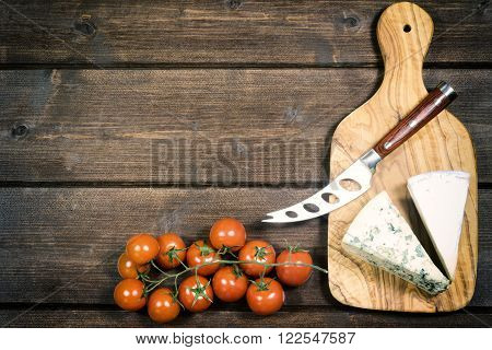 Cheese with white mold it and stainless steel cheese knife with wood handle are is lying on the board of olive wood. Cherry tomatoes are lying on a wooden board. Photo is edited as an vintage with dark edges.