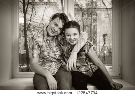 Black and white photo.  Boy and girl (brother and sister) sitting on a window sill