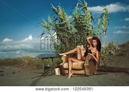 attractive young woman in bikini and top sit on armchair at sand beach hot sunny summer day, full body shot