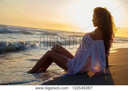 young woman sit at sand beach in long shirt enjoy in sunset bay the sea, side view full body shot
