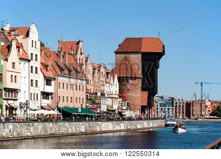 GDANSK, POLAND - AUGUST 8 2015: Gdansk old city in Poland with the oldest medieval port crane (Zuraw) in Europe, Weltawa river and people walking along the riverbank.